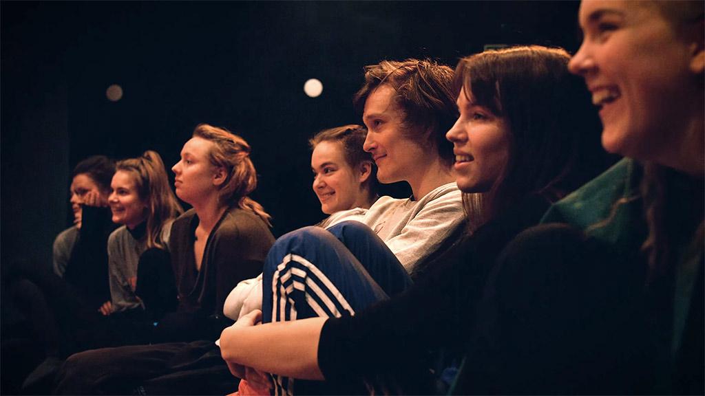 Koulun teatterilinjan opiskelijat katsomassa näyttelijän työn harjoituksia opiston teatterin salissa
